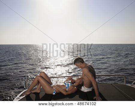 Amar par relajante en el borde de un yate por el mar
