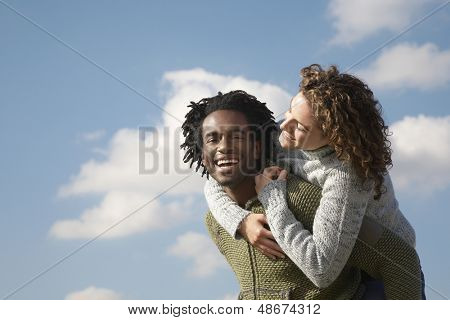 Portrait of cheerful young man piggybacking woman against cloudy sky