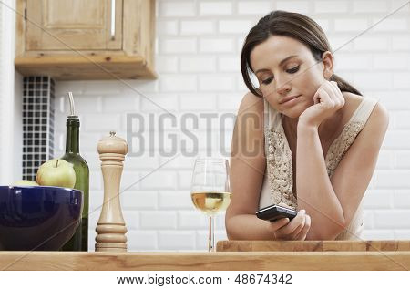Young woman text messaging through cellphone while leaning on wooden counter in kitchen