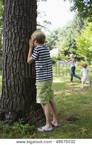 Boy standing by tree with eyes covered as children running in the background