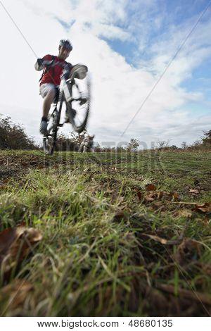 Full length of man performing wheelie on mountain bike in countryside