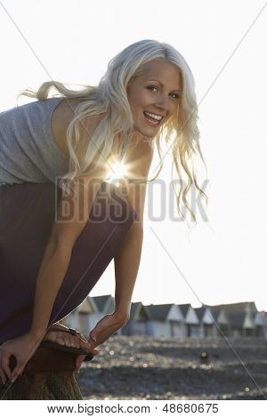 Side view portrait of playful young woman crouching at beach