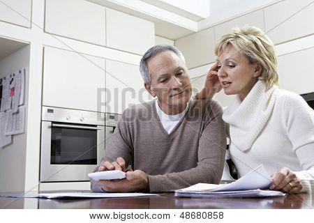 Middle aged couple making calculations using calculator at kitchen table
