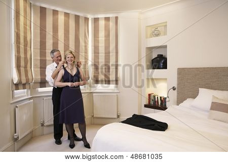 Full length of happy middle aged man fastening necklace on woman's neck in bedroom