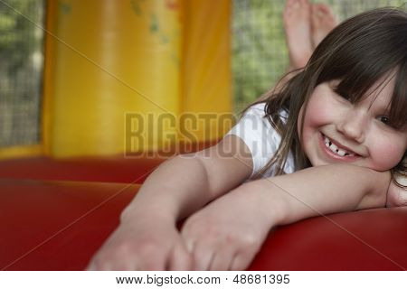 Closeup portrait of cheerful little girl lying in bouncy castle