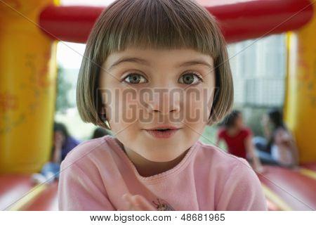 Closeup portrait of cute little girl in jumping castle