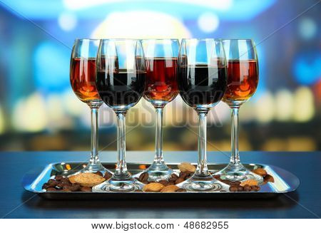 Glasses of liquors with almonds and coffee grains, on tray, on bright background