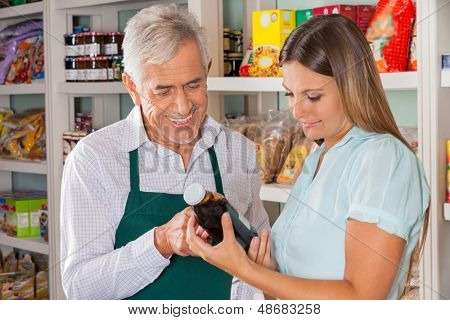 Senior male owner assisting female customer in choosing product at store