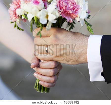 Groom handing over wedding bouquet - focus on rings