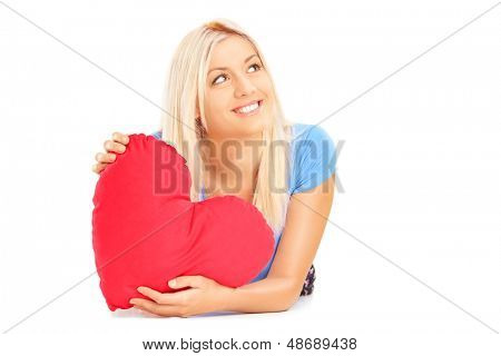 Smiling female lying down with red heart in her hands and wondering, isolated on white background