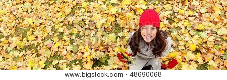 Autumn / fall banner background texture of leaves with happy woman. Panoramic fall concept portrait of smiling excited girl sitting on colorful autumn leaves outdoor in forest. Mixed race Asian girl.