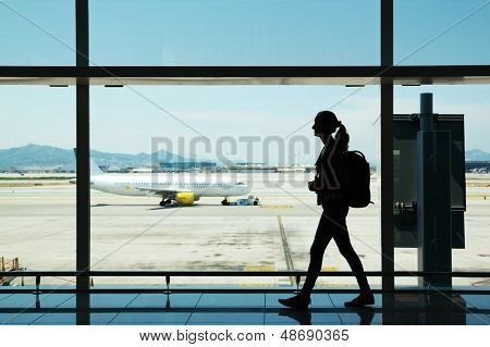 Silhouette of young woman walking at airport