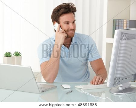 Office worker guy at desk using desktop computer laptop and mobile phone at work, smiling, looking at screen.