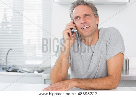 Happy man making phone call in kitchen sitting at counter