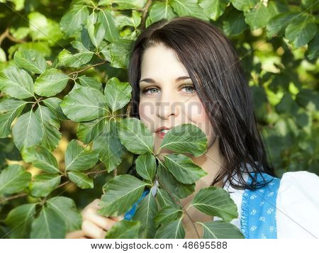 A beautiful young german woman in the green outdoor nature background