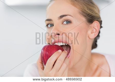 Attractive woman in her kitchen munching apple