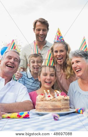 Happy extended family celebrating a birthday laughing at camera outside