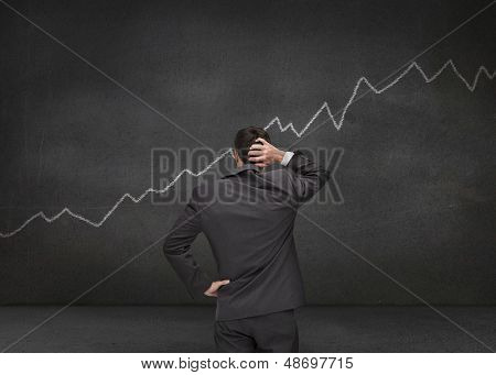 Hesitating businessman looking at white chart drawn on a black board