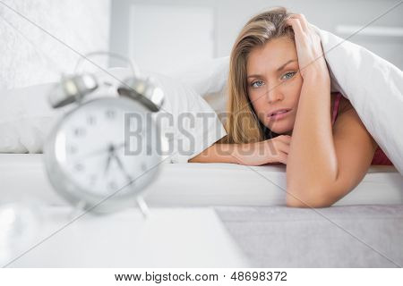 Exhausted blonde looking at camera with alarm clock in foreground at home in bedroom