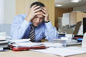 foto of upset  - Frustrated middle aged businessman sitting at office desk - JPG