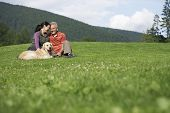 stock photo of heterosexual couple  - Happy middle aged couple and golden retriever relaxing on grass - JPG