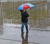 stock photo of rainy day  - a kid alone with an umbrella in a rainy day - JPG