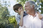 Closeup of a young boy whispering in grandfather's ear outdoors