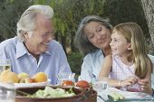 Grandparents with granddaughter sitting at garden table