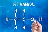 hand with pen drawing the chemical formula of ethanol