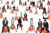stock photo of bouncing  - Businesspeople bouncing on inflatable balls isolated over white background - JPG