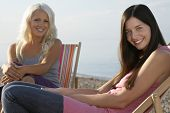 foto of herne bay beach  - Portrait of beautiful female friends sitting on deckchairs at beach - JPG