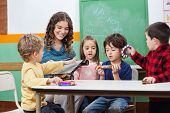 pic of daycare  - Children and teacher playing with musical instruments in preschool - JPG