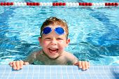 stock photo of 6 year old  - Smiling six year old boy in a sunny swimming pool - JPG