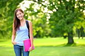 foto of fall day  - Student girl portrait holding books wearing backpack outdoor in park smiling happy going back to school - JPG