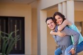 foto of piggyback ride  - Young woman piggyback riding her husband in front of their new home and smiling - JPG