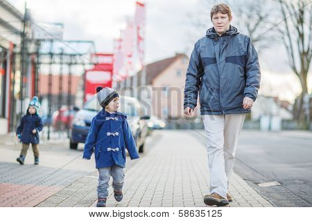 Father And Two Little Sibling Boys Walking On The Street In German Village.