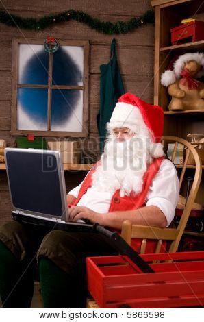 Santa Claus In Workshop Using Laptop