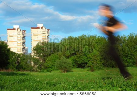Motion Blur Man Running In Park And Two Buildings