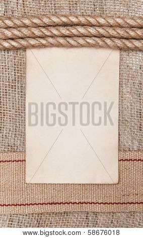 Aged Paper With Sacking Ribbon And Rope On Burlap