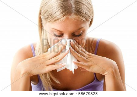 Young woman blowing into tissue