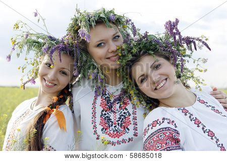 Three beauties in Ukrainian national costumes with smiles on their face