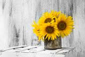 stock photo of bouquet  - Still life with sunflowers bouquet on matalic rusty cup on white wooden background - JPG