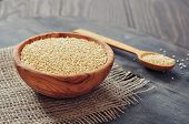 foto of quinoa  - Raw quinoa seeds in the wooden bowl on wooden background closeup - JPG