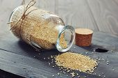 stock photo of quinoa  - Raw quinoa seeds in the glass bottle on wooden background closeup - JPG