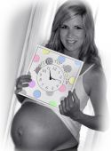 stock photo of bulging belly  - Mom smiles happily as she holds a clock announcing the arrival of her new baby - JPG