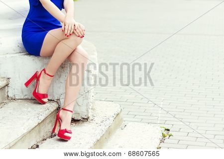 beautiful long legs girl in red shoes in blue dress sits in the city