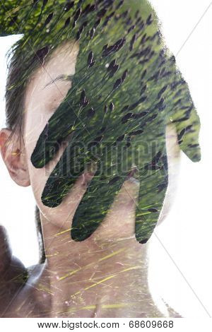 Double exposure portrait of woman covering her face with black glove combined with photograph of flower buds