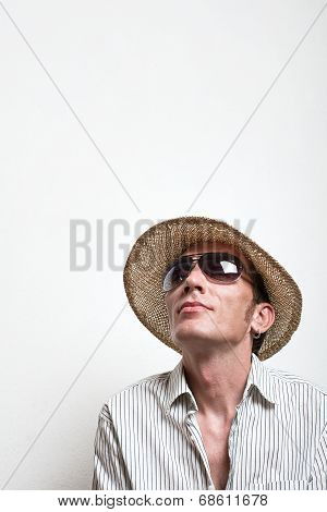 Young man in straw hat and sunglasses dreaming