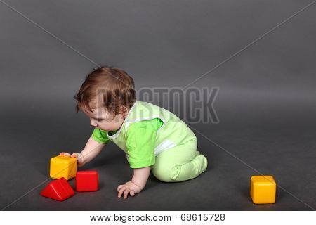 Baby in green sliders crawling on the floor with colored cubes