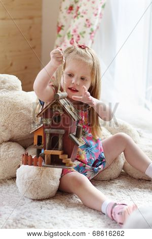 Pretty Blonde Little Girl Sits On Carpet Near Window And Plays With Toy House